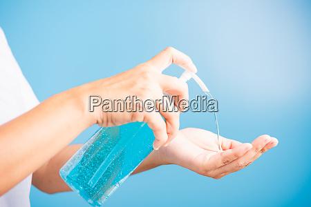 woman applying pump dispenser sanitizer alcohol