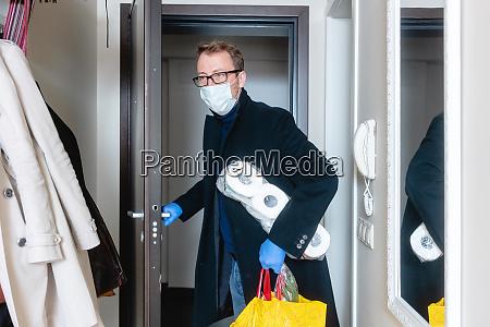 man wearing medical mask coming home
