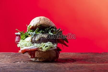 single hamburger on dark wood