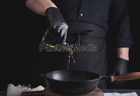 chef in black latex gloves pours