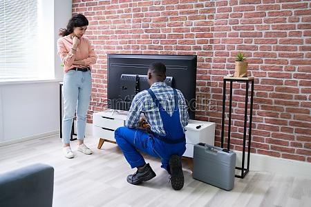 woman looking at technician repairing television