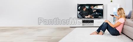 woman sitting on carpet watching television