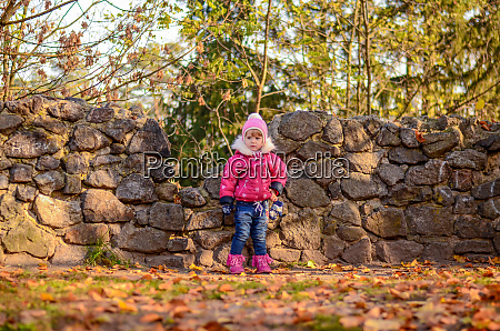 little girl in winter clothes stands