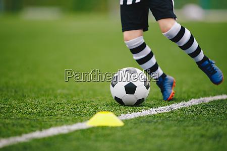 detail soccer player kicking ball on