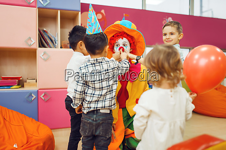 clown with cheerful children play counting