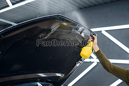 male worker wets car hood surface