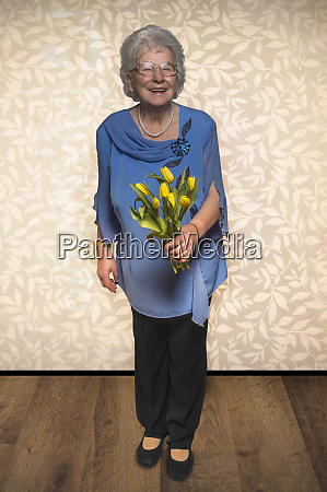 senior woman stands with tulip flowers
