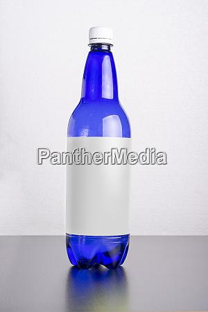 blue bottle with label on table