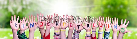 kids hands holding word kinderbetreuung means
