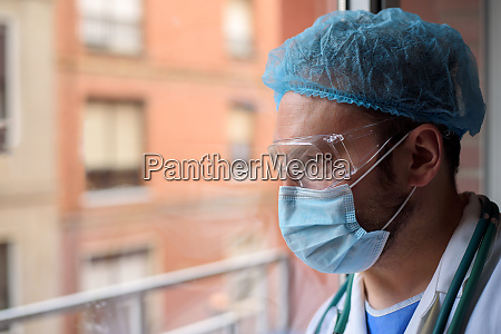 doctor with face mask looking through