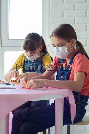 two sisters in medical masks play