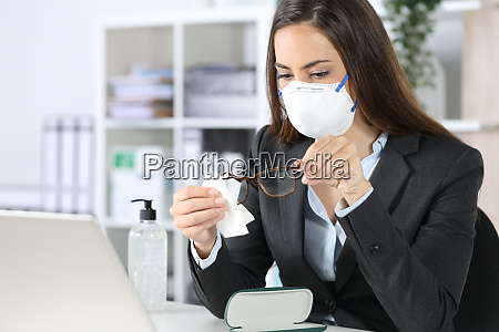 executive with mask cleaning glasses with