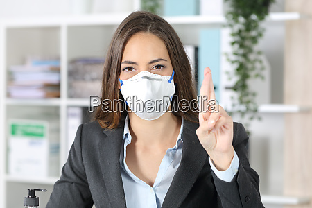 executive with mask crossing fingers looking