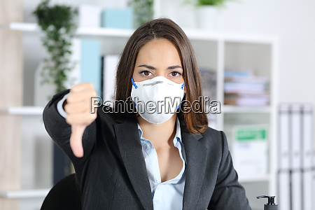 executive with mask gesturing thumbs down