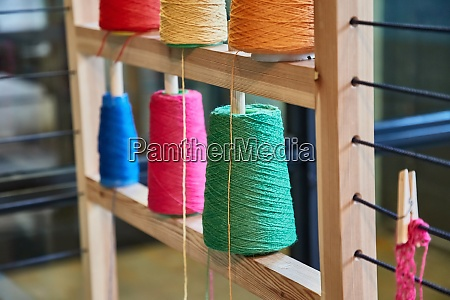 rack of colorful yarn rolls for