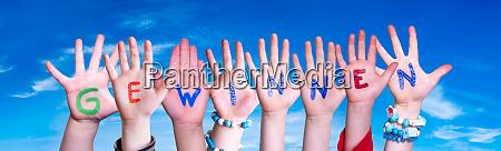 children hands building word gewinnen means
