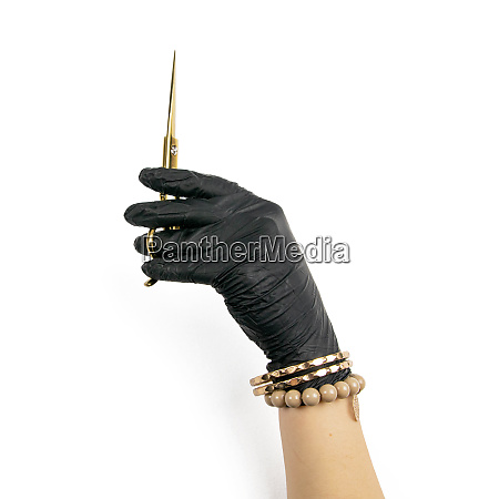 gloved hand holding a gold scisors
