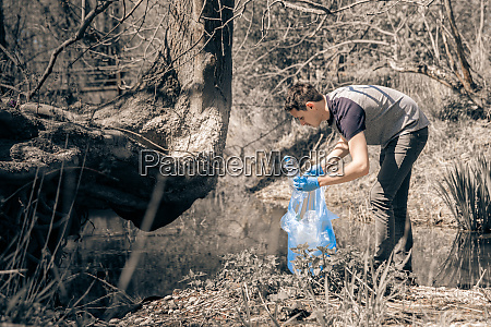 volunteer collects plastic waste in nature
