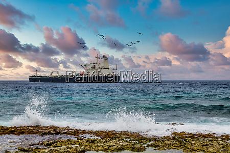 tanker sailing beyond crashing surf