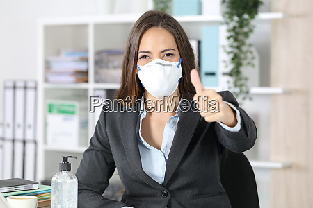 executive wearing mask with thumbs up