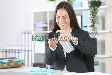 happy executive applying hand sanitizer at