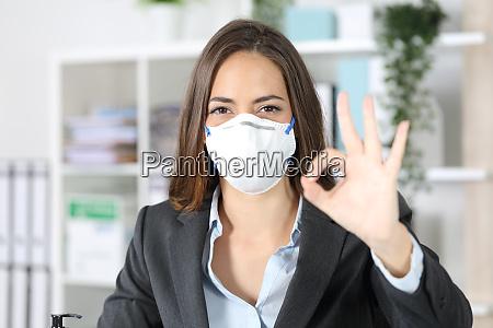 executive gesturing ok avoiding coronavirus at