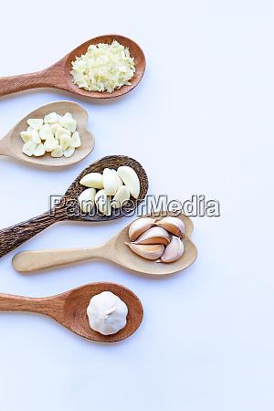 garlic on wooden spoon on white