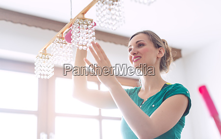 woman dusting a lamp during spring