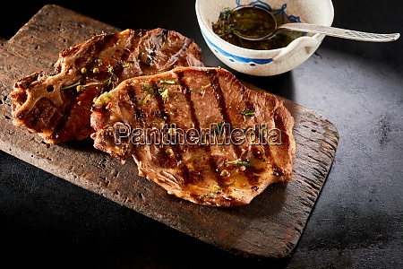 grilled steaks on timber board with