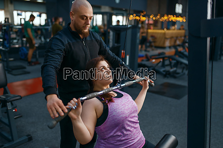 instructor helps to overweight woman gym