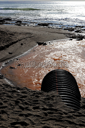 drainpipe with dirty water on shoreline
