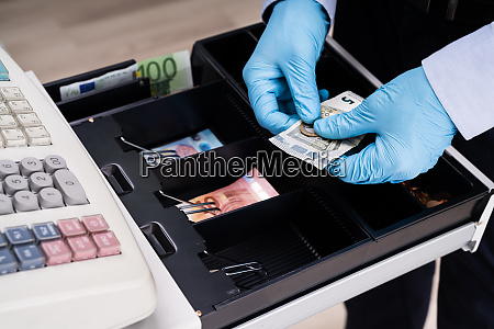 cashier working with register cash holding