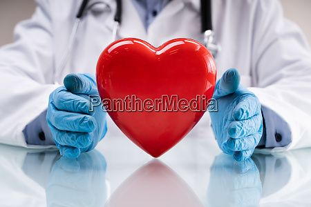 doctor with stethoscope red heart insurance