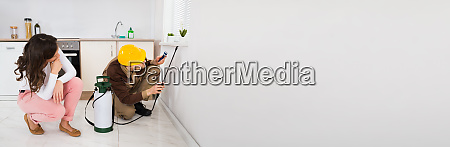 woman looking at worker spraying insecticide