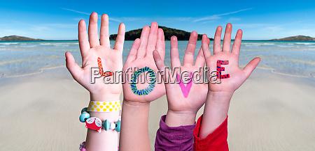 children hands building word love ocean