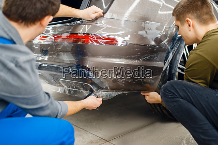 two workers applies car protection film