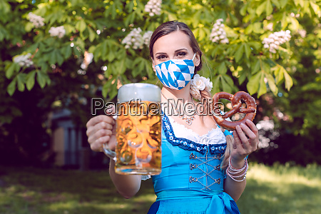 bavarian woman toasting with beer during