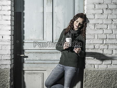 woman checking her messages and drinking