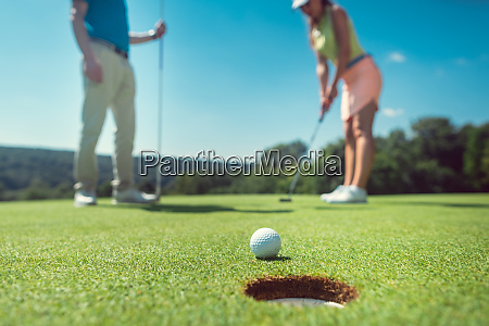 couple playing golf with the woman