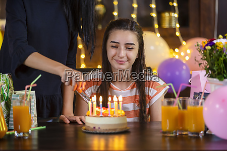 mother lighting candles on her daughter