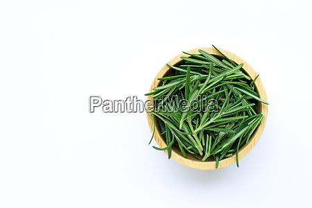 fresh rosemary leaves on wooden bowl