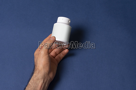male hand holding a white pillbox