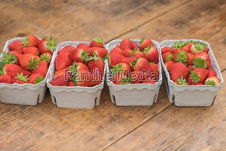 four strawberry market baskets with delicious