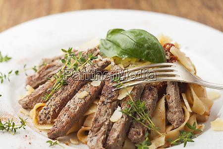 slices of steak on pasta