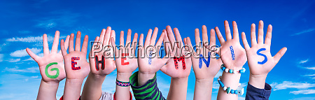 children hands building word geheimnis means