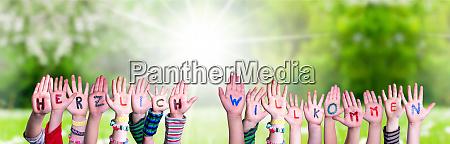 children hands building word herzlich willkommen