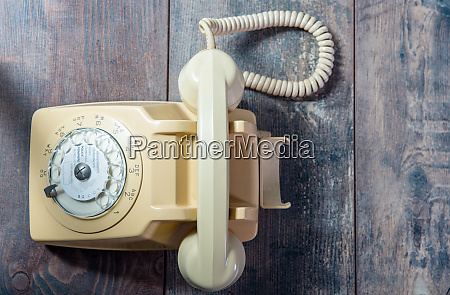 beige old telephone on wooden background
