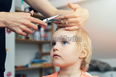 mother doing haircut for her child