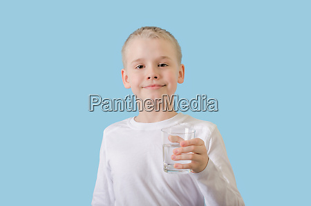 child holds glass of water in