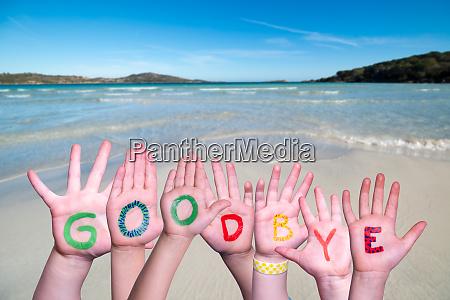 children hands building word goodbye ocean